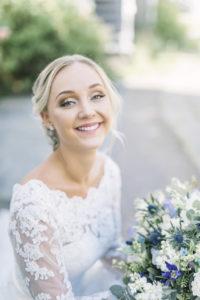 Brud med bröllopssmink, hårstyling och bröllopsbukett